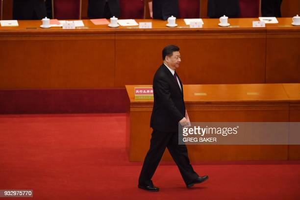 China's President Xi Jinping walks out to vote during the fifth plenary session of the first session of the 13th National People's Congress at the...