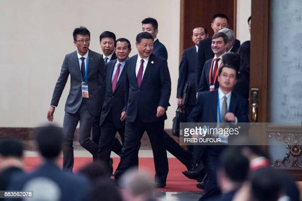 China's President Xi Jinping walks with Cambodia's Prime Minister Hun Sen and other leaders as they arrive at the opening ceremony of the 'CPC in...