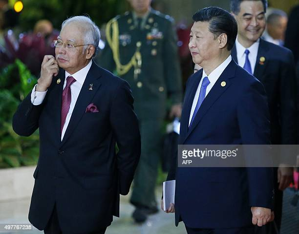 """China's President Xi Jinping walks with Malaysia's Prime Minister Najib Razak as they arrive for the official """"family photo"""" at the annual 21-member..."""