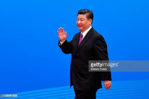 China's President Xi Jinping waves as he arrives for a press briefing at the end of the final day of the Belt and Road Forum at the China National...