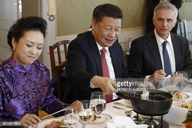 China's President Xi Jinping Xi's wife Peng Liyuan and Swiss Foreign Minister Didier Burkhalter eat Swiss cheese fondue during a lunch in Bern on...