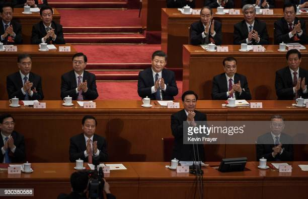 China's President Xi Jinpingcenter applauds after a vote on an amendment to the constitution during a session of the National People's Congress at...