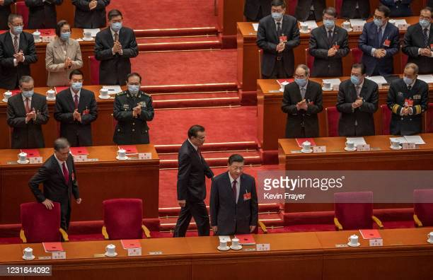 China's President Xi Jinping,center right, and Premier Li Keqiang, center left, are applauded by lawmakers as they arrive for the closing session of...