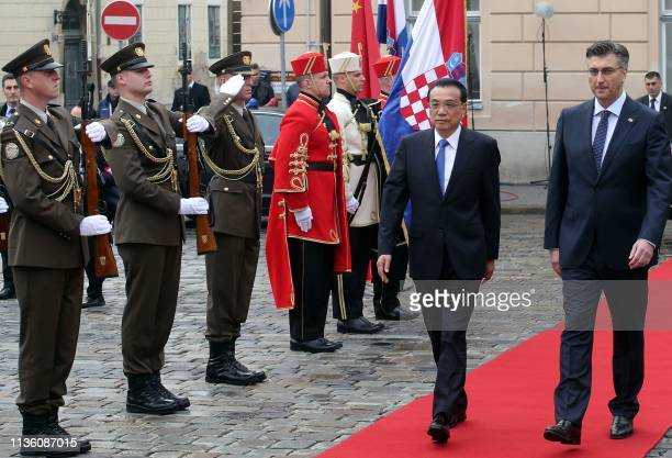 China's Prime Minister Li Keqiang and his Croatian counterpart Andrej Plenkovic review a guard of honour during a welcoming ceremony in Zagreb on...