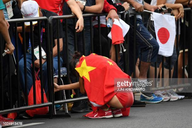 China's Qieyang Shijie reacts after finishing second in the women's 20km walk race competition during the 2018 Asian Games in Jakarta on August 29...