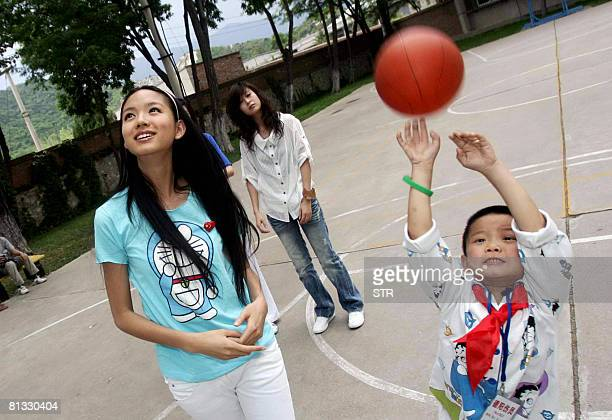 China's reigning Miss World 2007 Zhang Zilin visits a school in Beijing on June 2 where a group of children who survived the Sichuan earthquake are...