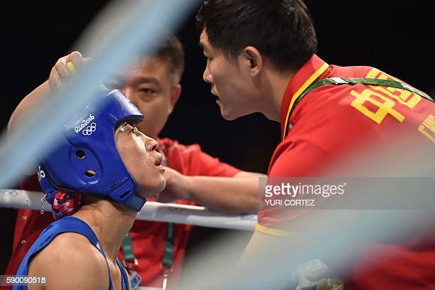 China's Ren Cancan is attended to as she fights Canada's Mandy Marie Brigitte Bujold during the Women's Fly Quarterfinal 2 match at the Rio 2016...