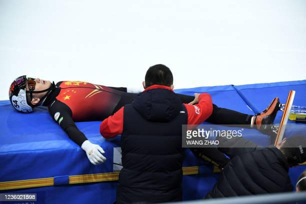 China's Ren Ziwei receives assistance from his coach during a pause in the men's 1500m quarter finals during the 2021/2022 ISU World Cup short track...
