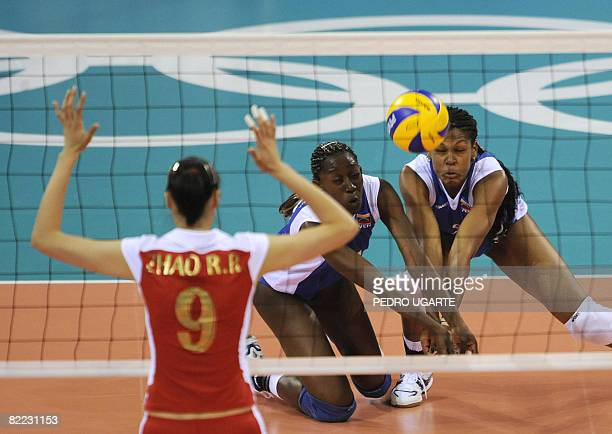 China's Ruirui Zhao looks as Venezuela's Jayce Andrade Andrade and Desire Glod reach for the ball during the preliminaries Pool A Volleyball match on...