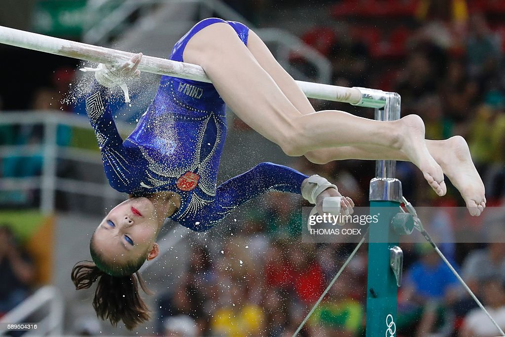TOPSHOT - China's Shang Chunsong chalks the bars before competing in the women's uneven bars event final of the Artistic Gymnastics at the Olympic Arena during the Rio 2016 Olympic Games in Rio de Janeiro on August 14, 2016. / AFP / Thomas COEX