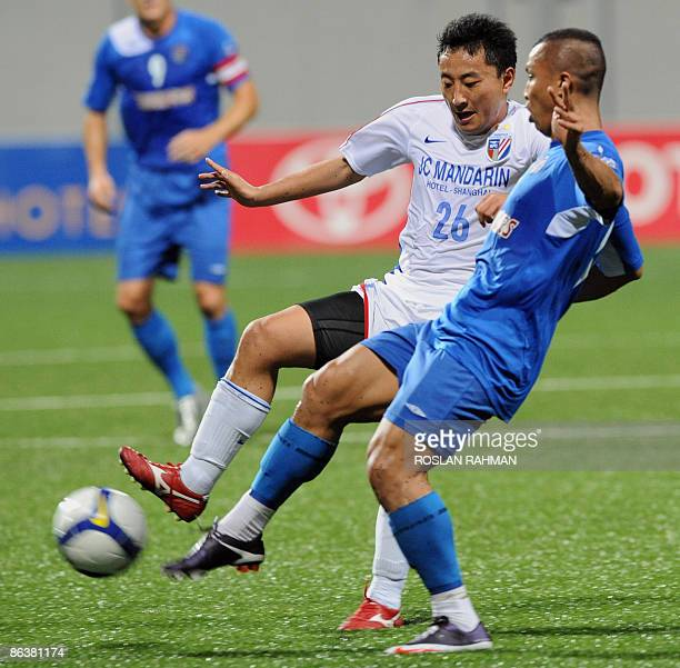 China's Shanghai Shenhua midfielder Wang Hongliang and Singapore Armed Forces FC midfielder Latiff fight for the ball during their AFC Champions...