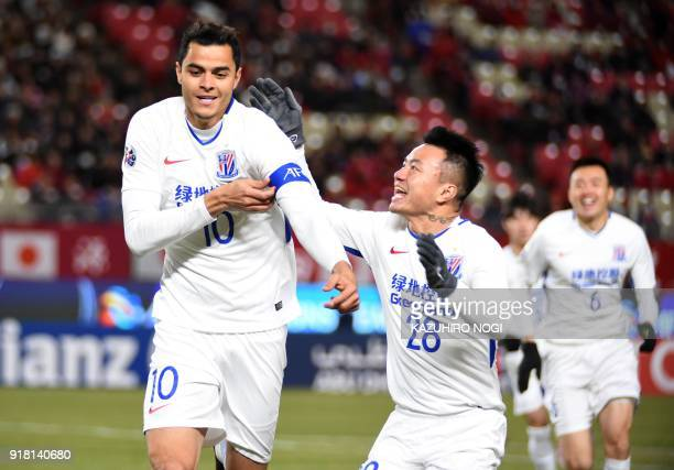 China's Shanghai Shenhua player Giovanni Moreno celebrates his goal with teammate Cao Yunding during their group stage football match against Japan's...