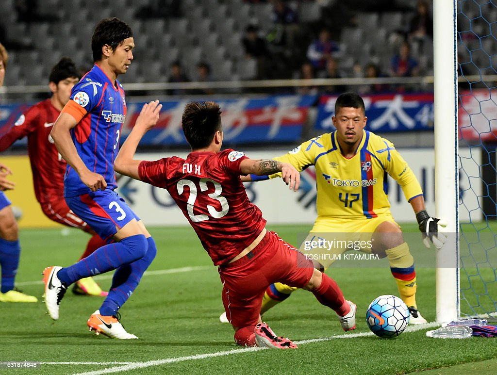 China's Shanghai SPIG defender Fu Huan (C) attempts to shoot in front of Japan's FC Tokyo goalkeeper Yuta Akimoto (R) during the AFC champions league round of 16 first match in Tokyo on May 17, 2016. / AFP / TOSHIFUMI