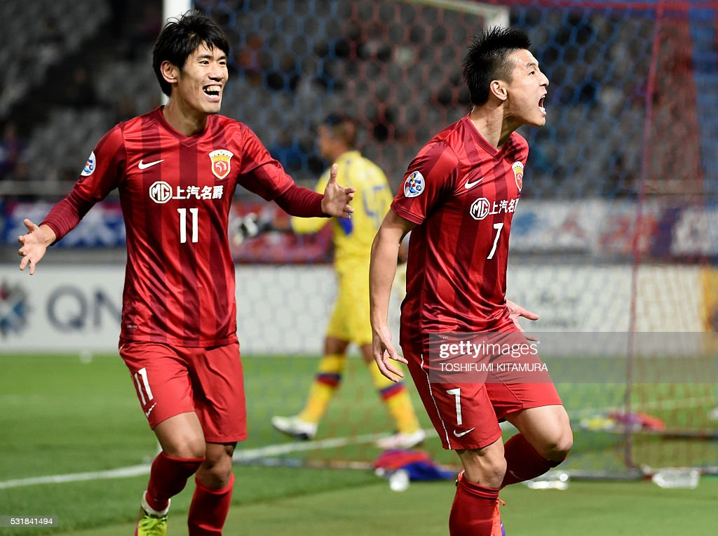 China's Shanghai SPIG forward Wu Lei (R) shouts in jubilation after scoring a goal beside forward Lu Wenjun (L) during the AFC champions league round of 16 first match against Japan's FC Tokyo in Tokyo on May 17, 2016. / AFP / TOSHIFUMI