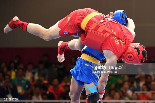 China's Shi Zhanwei fights against Iran's Mohsen Mohammadseifi during the men's sanda 70 kg final of the wushu event at the 2018 Asian Games in...