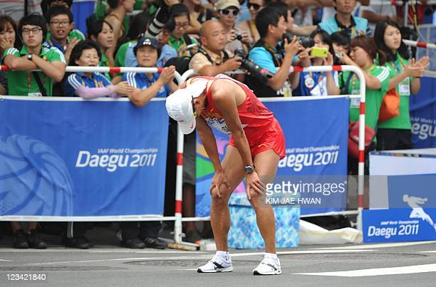 China's Si Tianfeng stands exhausted after finishing fourth in the men's 50 kilometre walk at the International Association of Athletics Federations...
