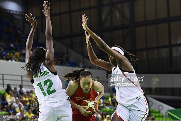 China's small forward Shao Ting runs between Senegal's power forward Mame Marie Sy and Senegal's forward Aya Traore during a Women's round Group B...
