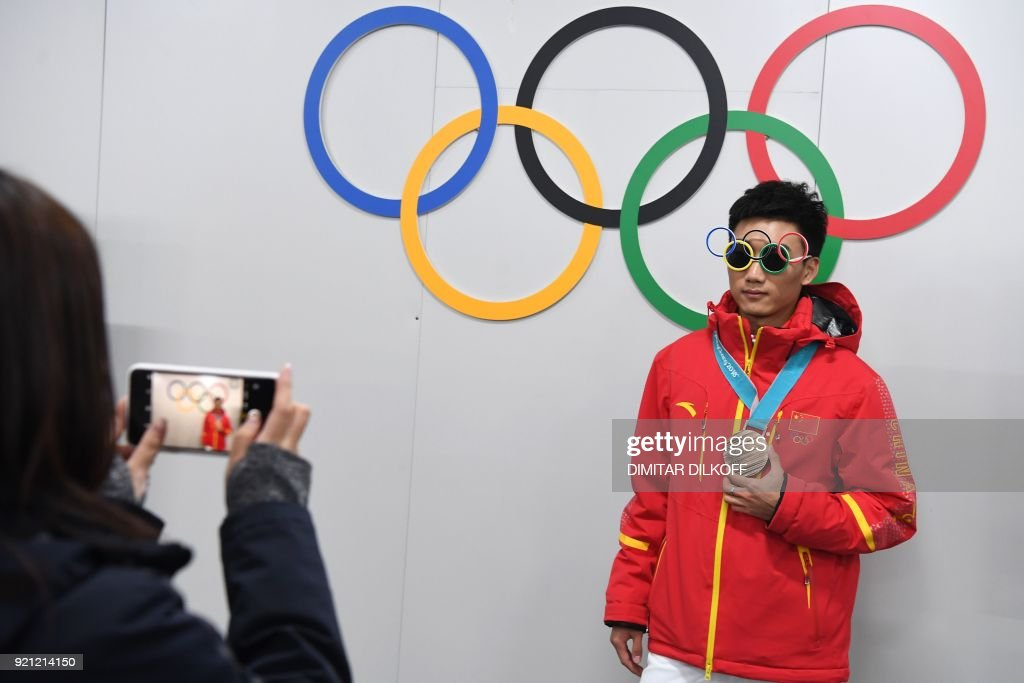 China's speed skating bronze medallist Gao Tingyu poses in front of Olympic rings backstage at the Athletes' Lounge during the medal ceremonies at the Pyeongchang Medals Plaza during the Pyeongchang 2018 Winter Olympic Games in Pyeongchang on February 20, 2018. / AFP PHOTO / Dimitar DILKOFF