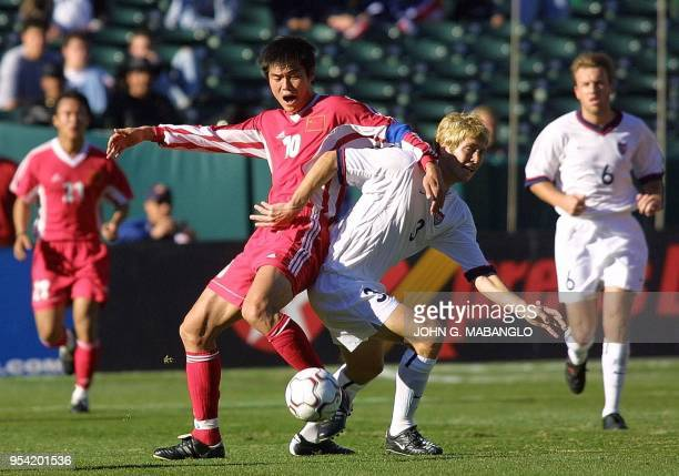 China's Su Maozhen battles for the ball against USA's Greg Berhalter during the first period of their friendly match 27 January in Oakland California...