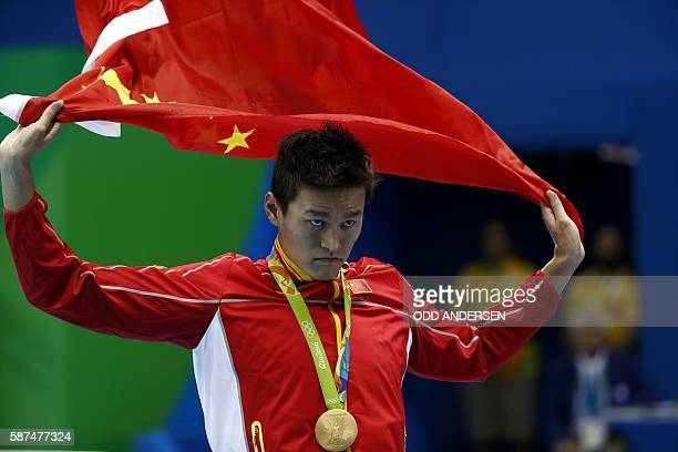 China's Sun Yang kisses his gold medal on the podium after he won the Men's 200m Freestyle Final during the swimming event at the Rio 2016 Olympic...