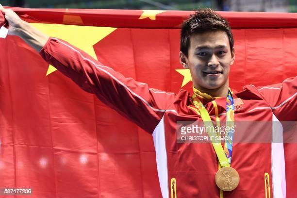 China's Sun Yang poses with his gold medal on the podium after he won the Men's 200m Freestyle Final during the swimming event at the Rio 2016...