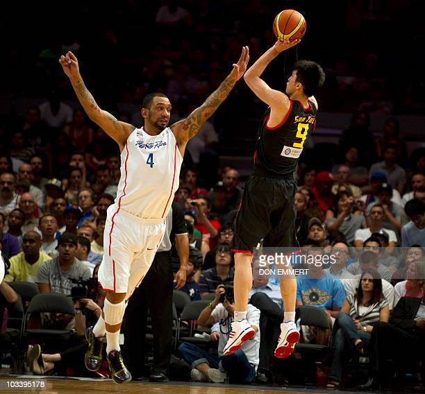 China's Sun Yue gets a shot off over Puerto Rico's Peter John Ramos during the Global Community Cup basketball exhibition game between Puerto Rico...