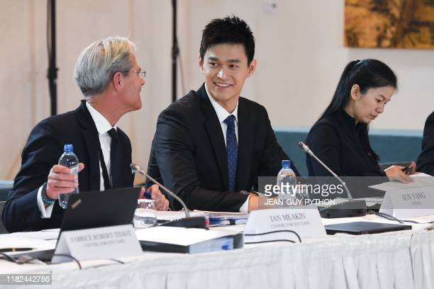 China's swimming star Sun Yang accused of smashing a blood vial with a hammer speaks with his counsel prior to a public hearing before the Court of...