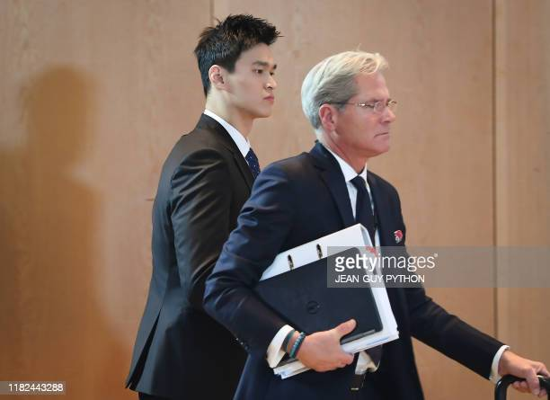 China's swimming star Sun Yang accused of smashing a blood vial with a hammer arrives next to his counsel Ian Meaking prior to his public hearing...