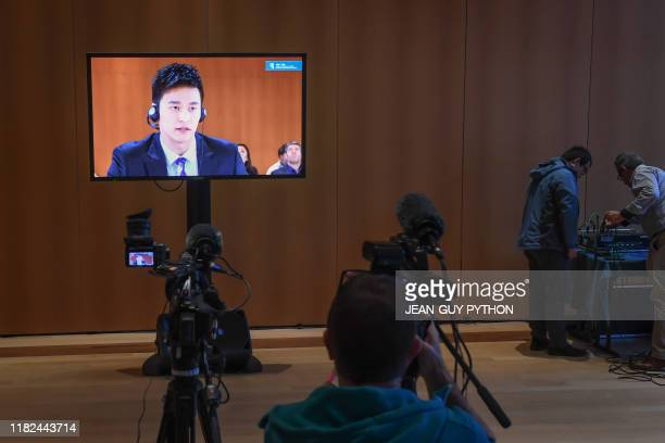 China's swimming star Sun Yang accused of smashing a blood vial with a hammer is seen on a TV screen delivering his testimony during a public hearing...