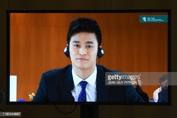 China's swimming star Sun Yang accused of smashing a blood vial with a hammer is seen on a TV screen during a public hearing before the Court of...