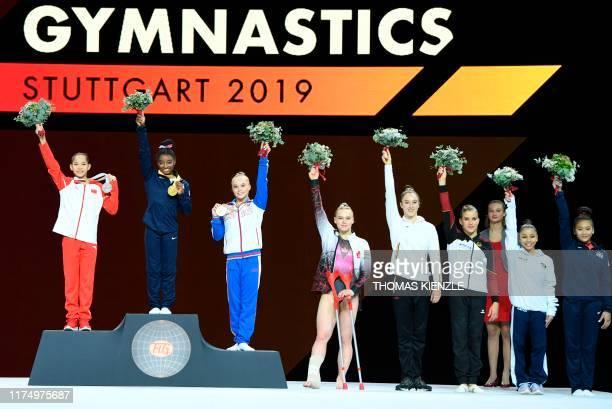 China's Tang Xijing , USA's Simone Biles and Russia's Angelina Melnikova pose on the podium as injured Canada's Elsabeth Black , Belgium's Nina...