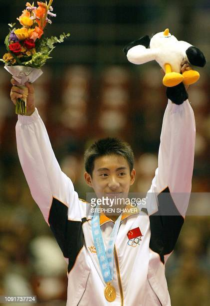 China's Teng Haibin celebrates after receiving his medal for the pommel horse event in the men's apparatus finals for the 14th Asian Games in Busan,...