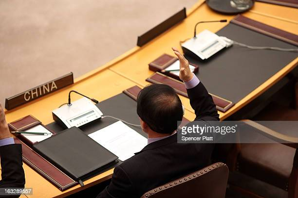 China's UN ambassador Li Baodong votes at a UN Security Council meeting on imposing a fourth round of sanctions against North Korea in an attempt to...