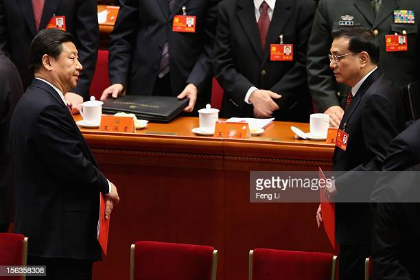 China's Vice President Xi Jinping and China's VicePremier Li Keqiang leave their seats after the closing session of the 18th National Congress of the...