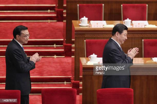 China's Vice President Xi Jinping and Vice Premier Li Keqiang walk as he arrives for the third plenary meeting of the National People's Congress at...