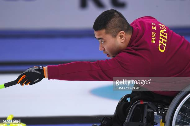 China's Wang Haitao throws a stone in the Wheelchair Curling gold medal game between China and Norway at the Gangneung Curling Centre during the...
