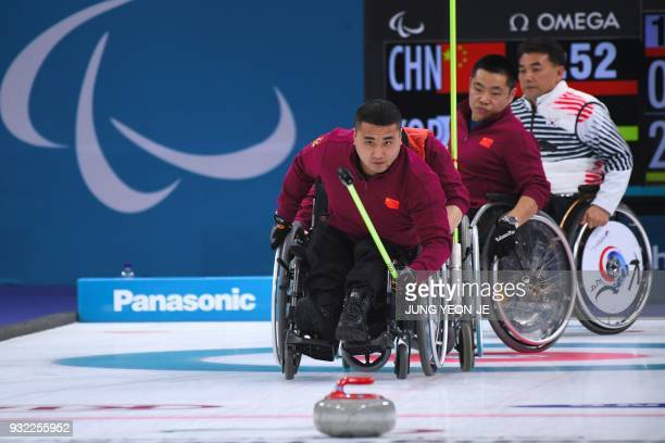 China's Wang Haitao throws a stone in the wheelchair curling round robin session between China and South Korea at the Gangneung Curling Centre during...