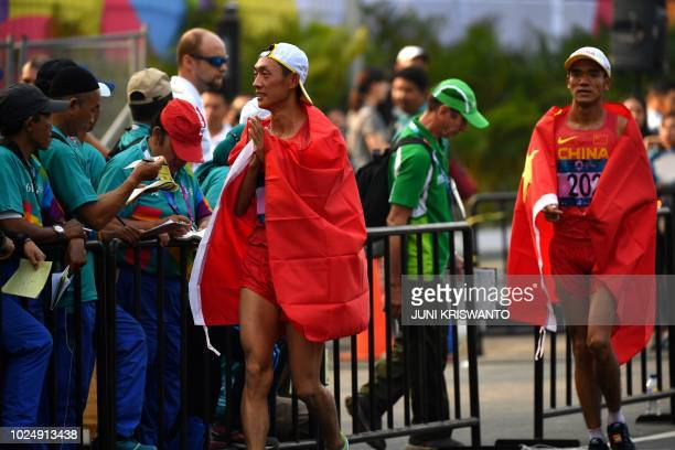 China's Wang Kaihua celebrates his victory as thirdplaced finisher Jin Xiangqin of China follows after finishing the men's 20km walk race competition...