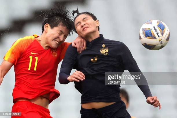 Chinas Wang Shanshan and Thailand's Natthakarn Chinwong compete for the ball during the women's Olympic football tournament qualifier match between...