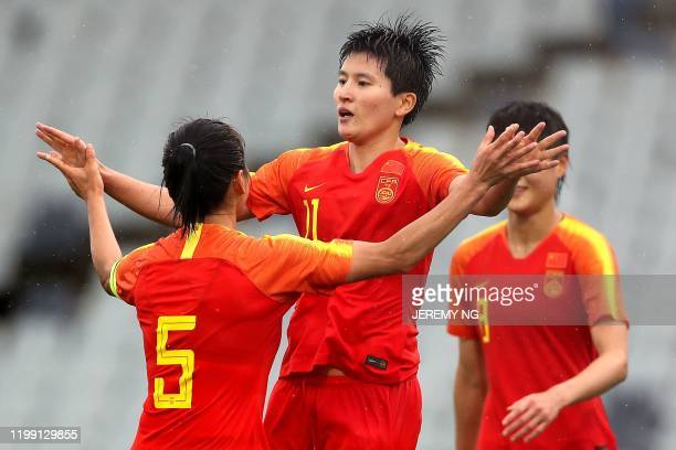 Chinas Wang Shanshan celebrates a goal with a teammate during the women's Olympic football tournament qualifier match between China and Thailand at...