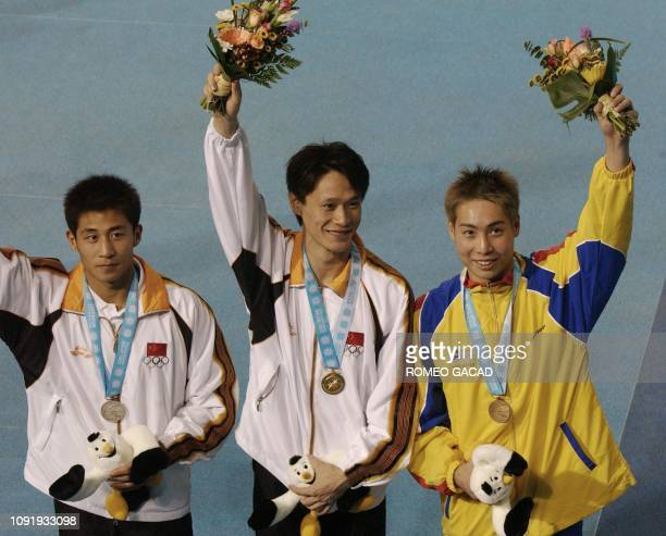 China's Wang Tian Ling poses on the podium with bronze medallist from Malaysian Yeoh Ken Nee and silver medallist Wang Feng of China after receiving...