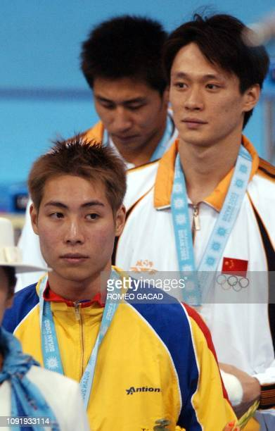 China's Wang Tian Ling poses on the podium with bronze medallist from Malaysia Yeoh Ken Nee and silver medallist Wang Feng of China after receiving...