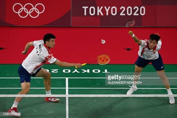 China's Wang Yilyu hits a shot next to China's Huang Dongping in their mixed doubles badminton quarter final match against South Korea's Chae...
