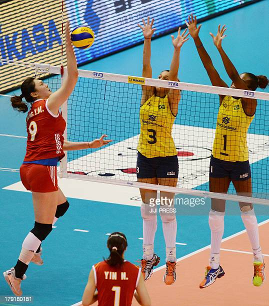 China's Wang Yimei spikes the ball against Brazil's Danielle Lins and Fabiana Claudino duriing their match of the women's volleyball World Grand Prix...