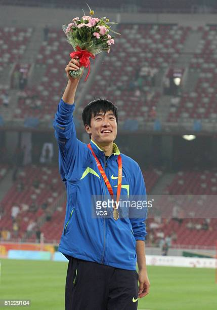 China's world and Olympic champion Liu Xiang celebrates on the winners' podium with his gold medal for the Men's 110m Hurdles final during the Good...