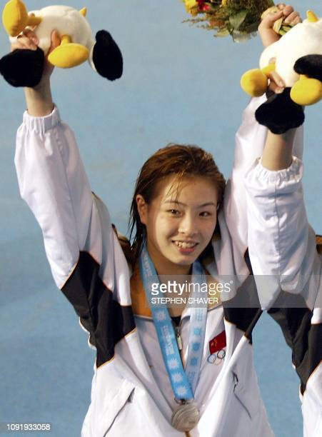 China's Wu Minxia celebrates winning the silver medal during an awards ceremony for the women's 3metre springboard final 10 October 2002 at the 14th...