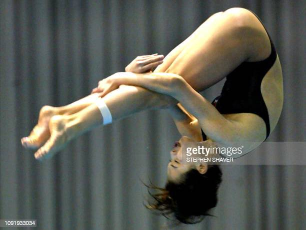 China's Wu Minxia does a backwards somersault during the women's 3metre springboard final 10 October 2002 at the 14th Asian Games in Busan Teammate...