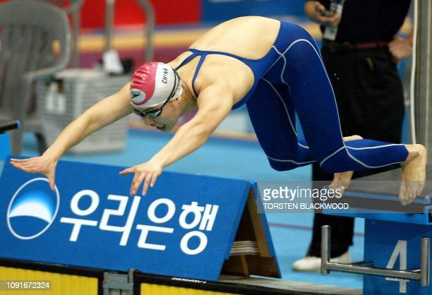 China's Xi Zheng dives from the blocks at the start of the women's 100m butterfly heat at the 14th Asian Games in Busan 02 October 2002 Xi set the...