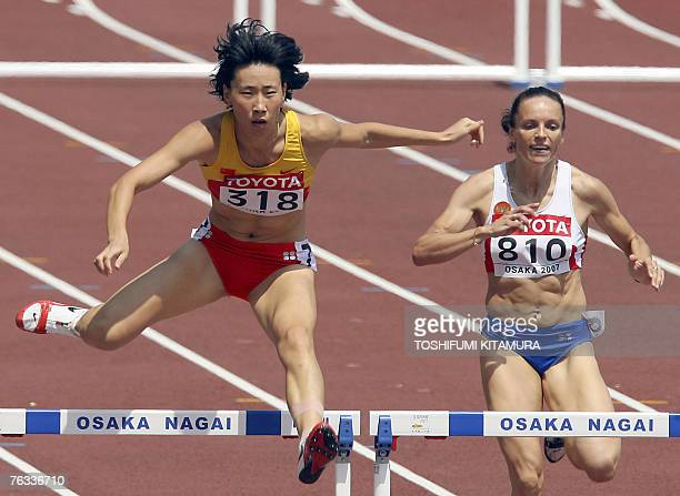 China's Xiaoxiao Huang and Russia's Isakova Yevgeniya compete during the women's 400m hurdles first round 27 August 2007 at the 11th IAAF World...