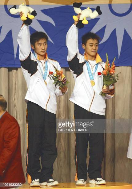 China's Xu Hao and Hu Jia celebrate after receiving the gold in the men's 10m Synchronized Diving event 08 October 2002 at the 14th Asian Games in...